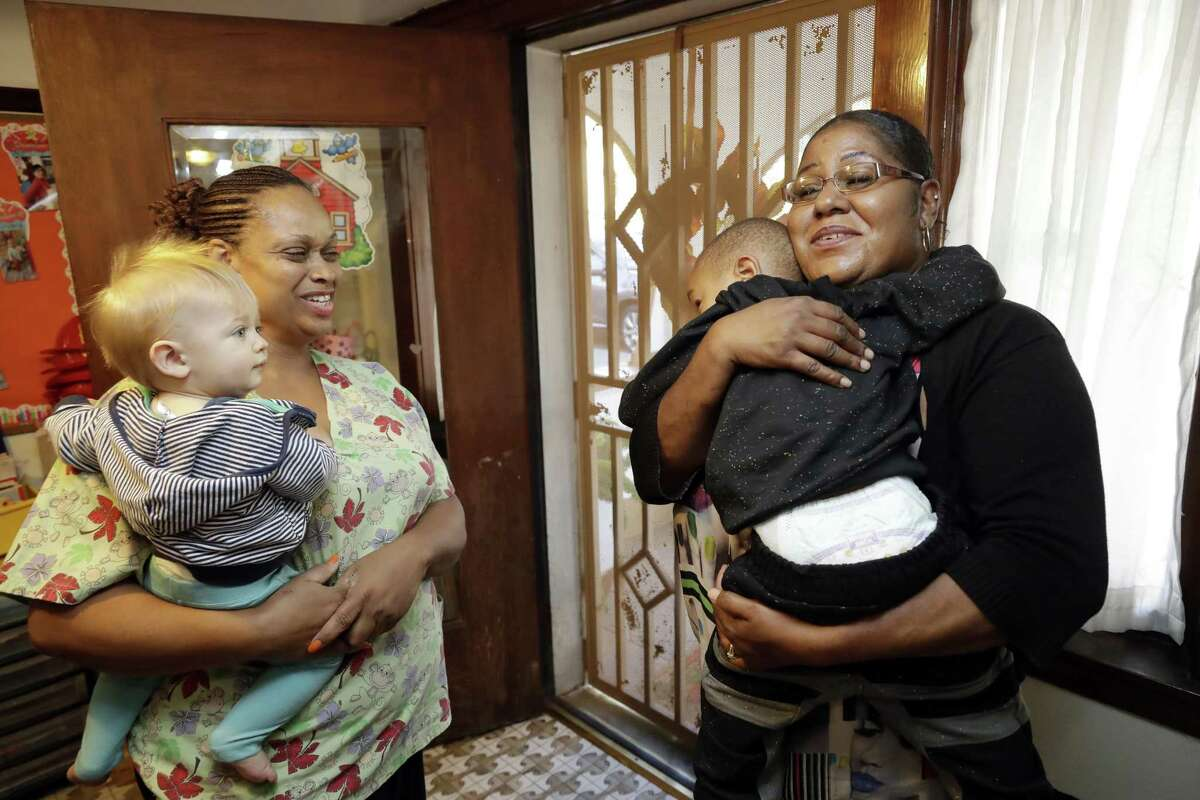 Nancy Harvey (left), owner of Lil' Nancy's Primary Schoolhouse, chats with one her clients, Tamara Purifoy, as Purifoy picks up her son Alonzo Simpson, 3.