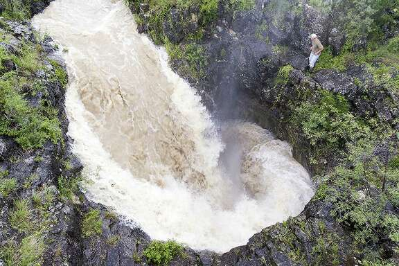 Chester, an employee of a private ranch two hours west of San Antonio, stands on the edge of a large sink hole Thursday, May 19, 2016 as about 500 cubic feet per second of water go down the hole into the Edwards Aquifer. The sink hole is one of the largest single recharge features for the aquifer.