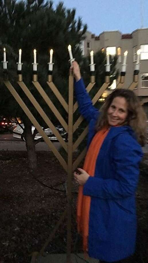 Shari Weissner lights a candle on the menorah that was stolen Sunday from Washington Square Park. Photo: North Beach Chabad Of San Francisco