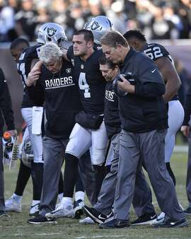 Oakland Raiders quarterback Derek Carr (4) is assisted off the field after sustaining an injury after being tackled by the Indianapolis Colts' Trent Cole in the fourth quarter at the Coliseum in Oakland, Calif., on Saturday, Dec. 24, 2016. (Jose Carlos Fajardo/Bay Area News Group/TNS)