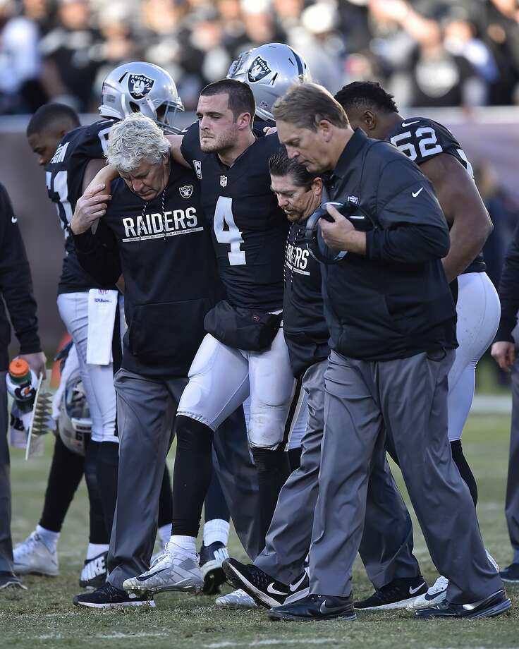 Oakland Raiders quarterback Derek Carr (4) is assisted off the field after sustaining an injury after being tackled by the Indianapolis Colts' Trent Cole in the fourth quarter at the Coliseum in Oakland, Calif., on Saturday, Dec. 24, 2016. (Jose Carlos Fajardo/Bay Area News Group/TNS) Photo: JOSE CARLOS FAJARDO, TNS