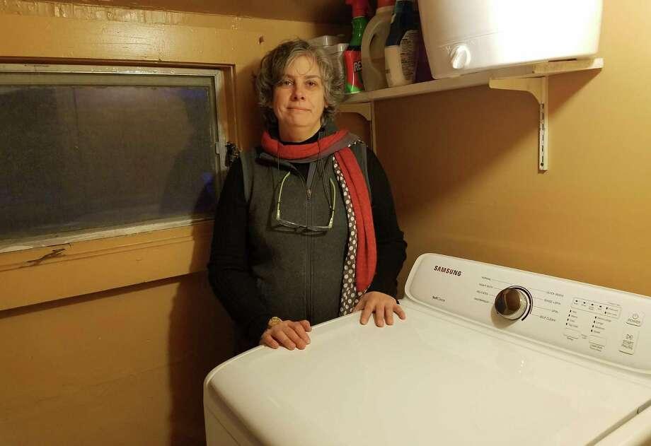 Jennifer Pruden of Nassau stands with her recalled Samsung washing machine. (Chris Churchill / Times Union)