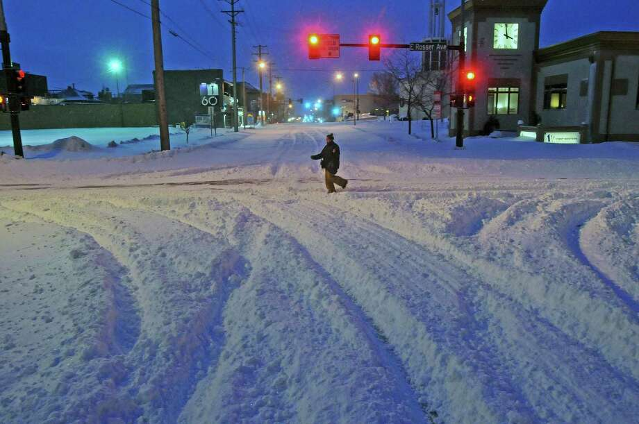 Madori Griffin, who says her car was snowed in, makes her way through an intersection while walking to work in the intensive care unit of Sanford Hospital early Monday, Dec. 26, 2016, in Bismarck, N.D. The combination of freezing rain, snow and high winds that forced the shutdown Sunday of vast stretches of highways in the Dakotas continued into Monday morning, and authorities issued no-travel warnings for much of North Dakota. (Tom Stromme/The Bismarck Tribune via AP) ORG XMIT: NDBIS202 Photo: Tom Stromme / The Bismarck Tribune