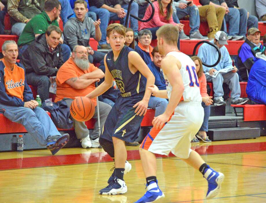 Father McGivney junior Dan Jones, left, is guarded by Flora's Trevin Smith during Monday's game at the Vandalia Holiday Tournament.