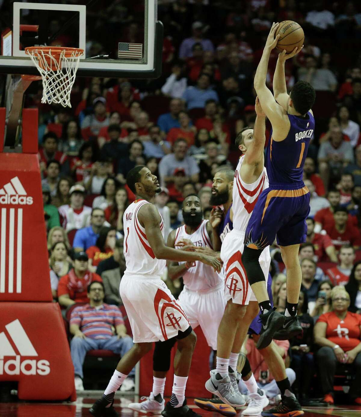 Phoenix Suns guard Devin Booker (1) shoots over Houston Rockets forward Ryan Anderson (3) as forward Trevor Ariza (1) watches in the first half of an NBA basketball game on Monday, Dec. 26, 2016 in Houston. (AP Photo/Bob Levey)
