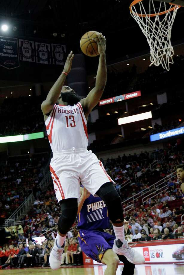 Houston Rockets guard James Harden (13) drives past Phoenix Suns guard Devin Booker (1) to the basket for a layup in the first half of an NBA basketball game on Monday, Dec. 26, 2016 in Houston. (AP Photo/Bob Levey) Photo: Bob Levey, Associated Press / AP