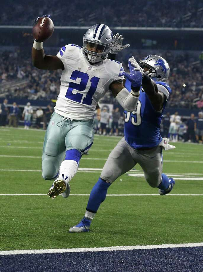 Ezekiel Elliott leaps into the end zone ahead of Detroit's Tahir Whitehead for a second-half touchdown during Dallas' victory at AT&T Stadium. Photo: Michael Ainsworth / Associated Press / FR171389 AP