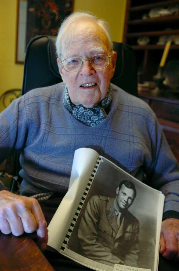 World War II veteran Daniel Badger holds a picture of himself during the World War II, at home in Greenwich on Moday, May 24, 2010.  He was in the U.S. Army core, and was part of the Normandy invasion at Utah Beach. Photo: Helen Neafsey / Greenwich Time