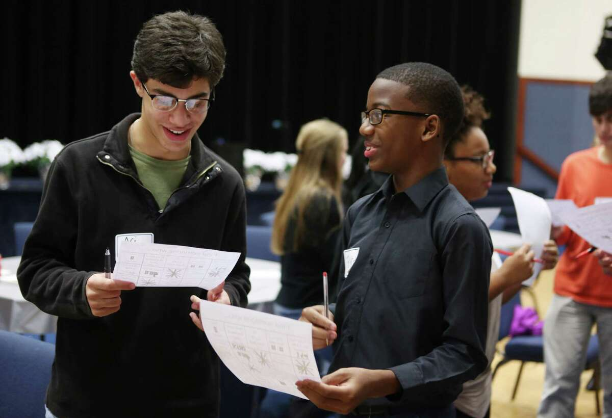 Ari Schwartzberg (left), 17, and Brycen August, 13, do a scavenger hunt together during an event inviting members of Congregation Beth Yeshurun to spend an evening of fellowship with members of The Church of Bethelé?•s Family, Sunday, Nov. 20, 2016, in Houston. ( Mark Mulligan / Houston Chronicle )