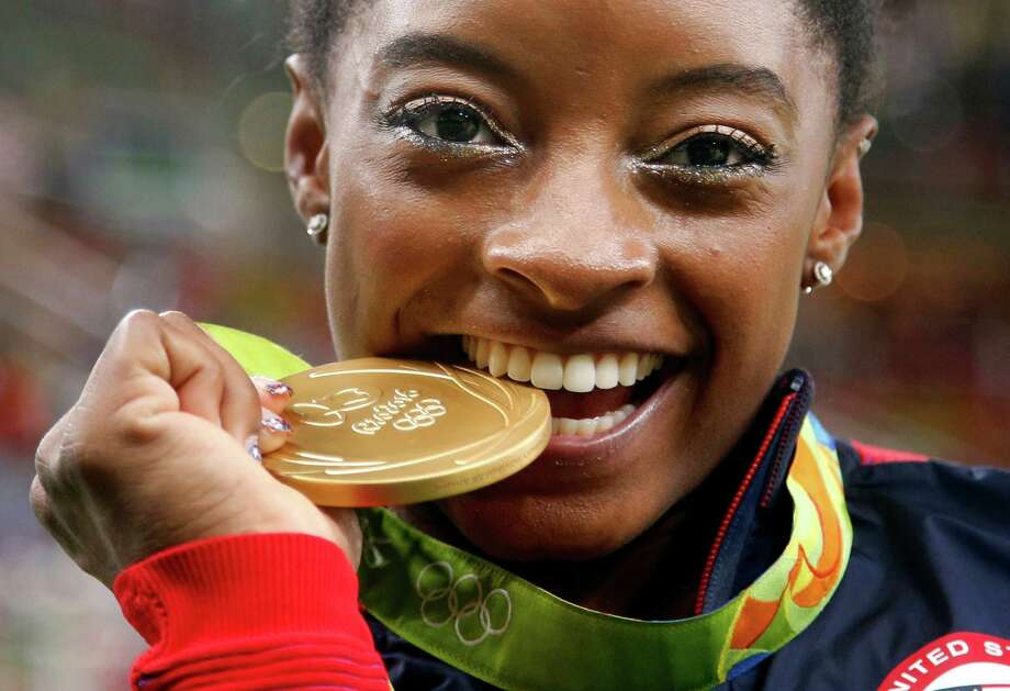In this Aug. 11, file photo, United States' Simone Biles bites her gold medal for the artistic gymnastics women's individual all-around final at the 2016 Summer Olympics in Rio de Janeiro, Brazil. Reuters reported that Olympic medals received in Rio were rusting or chipping. Photo: Dmitri Lovetsky, STF / Copyright 2016 The Associated Press. All rights reserved. This material may not be published, broadcast, rewritten or redistribu