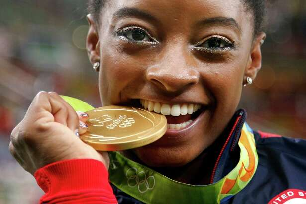 In this Aug. 11, file photo, United States' Simone Biles bites her gold medal for the artistic gymnastics women's individual all-around final at the 2016 Summer Olympics in Rio de Janeiro, Brazil. Biles was selected as the AP Female Athlete of the Year on Dec. 26.