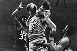 Spurs' Billy Paultz (center) finishes off a dunk on Rich Jones (33) during Game 2 of the ABA semifinal playoff series with the New York Nets on April 14, 1976.