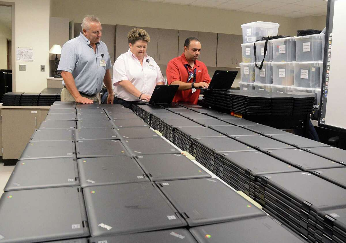 Craig Gentry, Klein ISD Manager Technology Services, Karen Fuller, Chief Technology Officer, and Philip Perez, Supervisor Technical Services, examine some of the 1.500 laptop computers that will be given to students at Klein ISD's Ulrich Intermediate School. Photograph by David Hopper