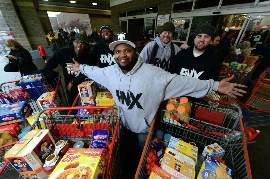 Local rapper FNX and his crew, from left, Mark Robinson, Anthony Grant, Marc Alan and Billy Gardella, finish shopping for food at Costco in Norwalk on Saturday to help feed several needy families using money raised through a GoFundMe campaign. Photo: Erik Trautmann / Hearst Connecticut Media / Norwalk Hour