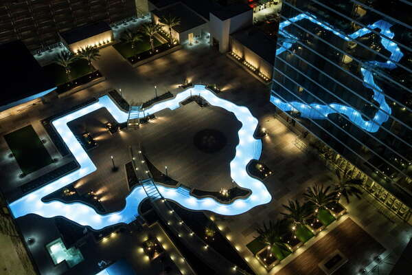 The Texas-shaped lazy river pool is lit up during the grand lighting ceremony at the Marriott Marquis hotel on Monday, Dec. 26, 2016, in Houston.