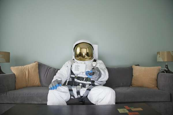 Astronaut in living room sitting on couch watching TV, changing channel with remote control.