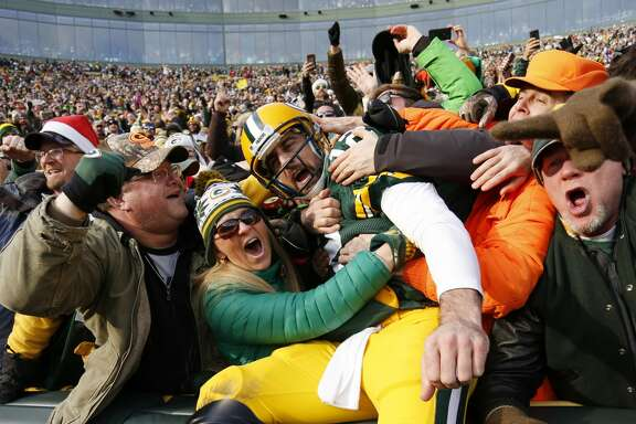 Green Bay Packers' Aaron Rodgers celebrates his touchdown run with fans during the first half of an NFL football game against the Minnesota Vikings Saturday, Dec. 24, 2016, in Green Bay, Wis. (AP Photo/Matt Ludtke)