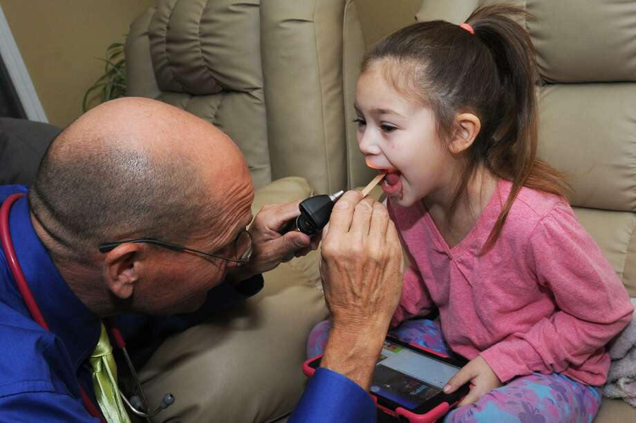 Charles Wetmore, a APRN and CPNP with Pediatric House Call Solutions, checks Kaelah Yanez, 5, during a routine house call to the Yanez family home in Stratford, Conn. Nov. 29, 2016. Photo: Ned Gerard / Hearst Connecticut Media / Connecticut Post