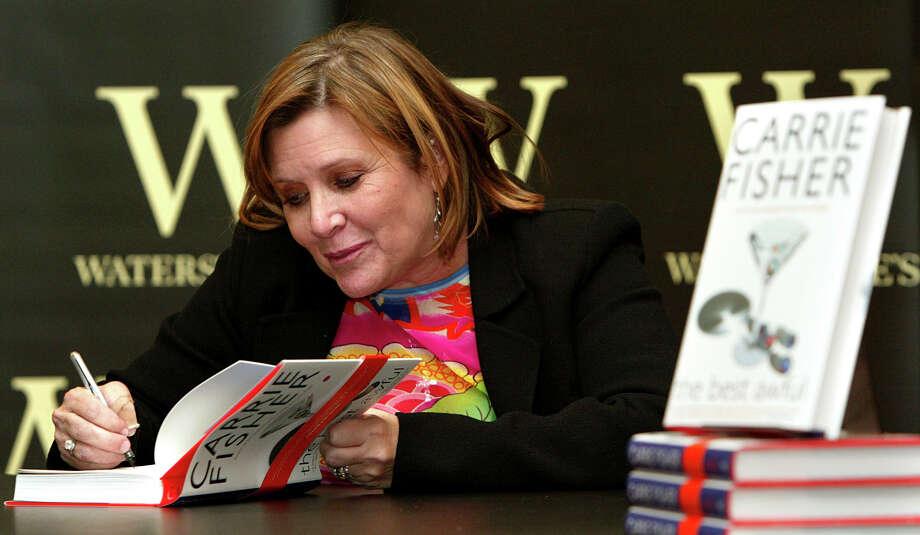 """ARCHIVO - Carrie Fisher firma su nuevo libro """"The Best Awful"""" en un evento promocional en Londres en una fotografía de archivo del 20 de febrero de 2004. Fisher falleció el martes 27 de diciembre de 2016, informó un publicista. Tenía 60 años. (Foto AP/John D. McHugh, archivo) Photo: John D. McHugh, ASSOCIATED PRESS / AP"""