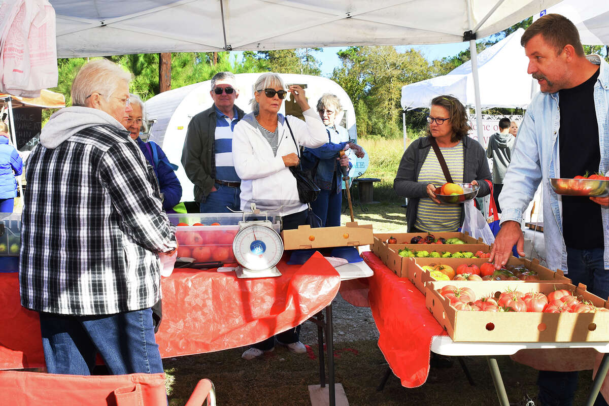 Customers gather around Susan Hughes, left, at her booth to buy her tomatoes and vegetables at the Farmer's Market on Tamina.