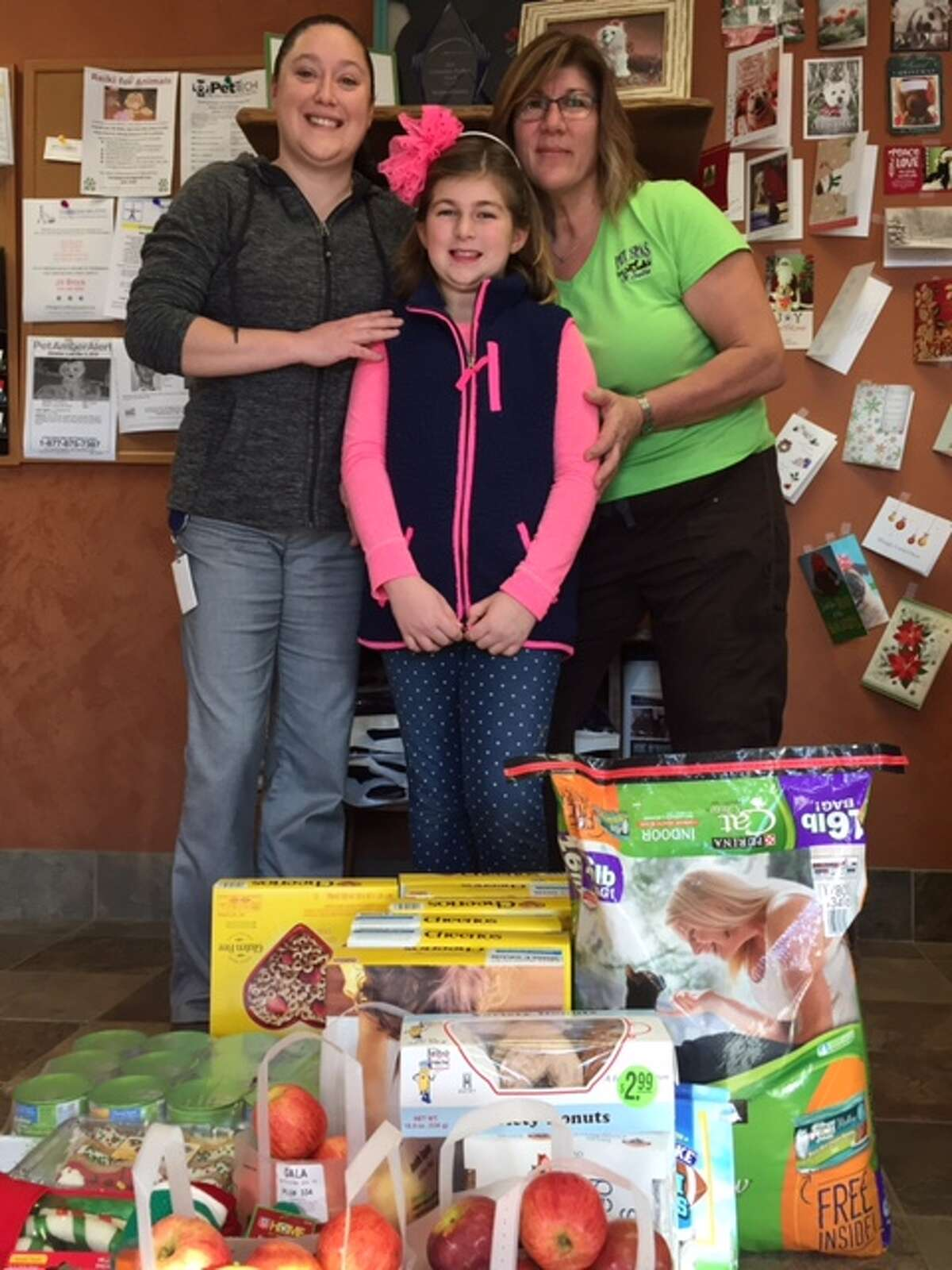 Seen here are Marissa Hebert from Pawsome Pets Presevere, Mallory Heider, 9, and Tracy Muscatello, founder of HeartsHerd Animal Sanctuary (Submitted photo)
