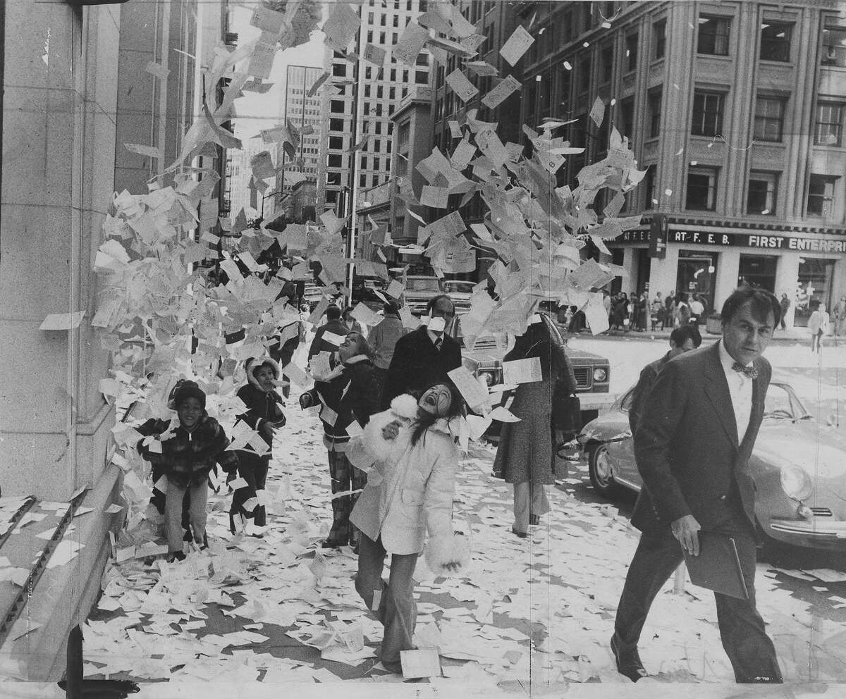 Young people throwing calendar book pages into the air in San Francisco on December 31, 1976.