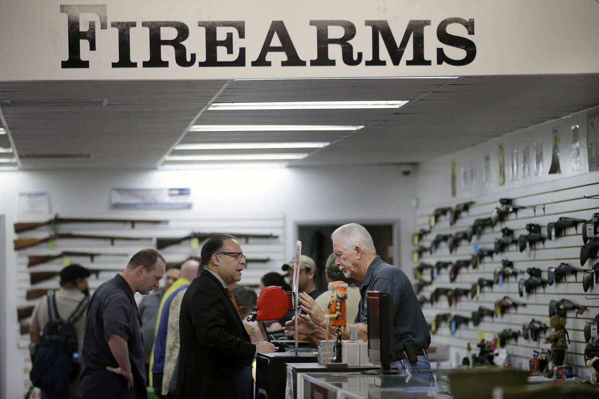 FILE - In this Dec. 9, 2015, file photo, sales associate Mike Conway, right, shows Paul Angulo guns at Bullseye Sport gun shop in Riverside, Calif. With six new gun control bills signed by California's Gov. Jerry Brown in July 2016, sales of semi-automatic rifles have more than doubled in California over last year. (AP Photo/Jae C. Hong, File)