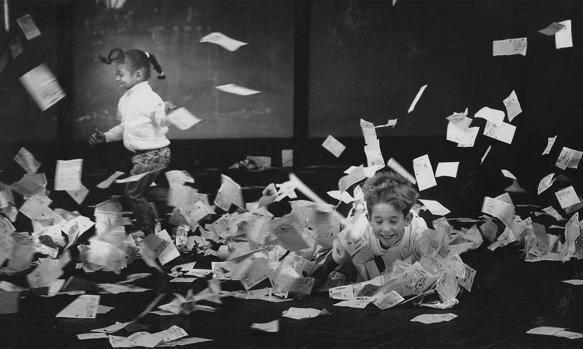 On the last working day of the year, in San Francisco, workers in the financial district celebrated by tossing their 1989 calendar pages out of their office windows, onto the streets below, to the delight of these two kids. December 31, 1988.