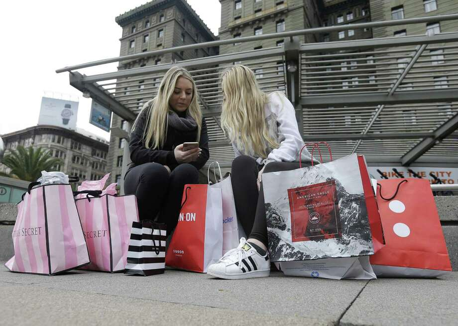 Maddy (left) and her friend Maggie sit with their shopping bags at Union Square in San Francisco. Research firm Customer Growth Partners raised its holiday sales estimate to a 4.9 percent gain over last year to $637 billion. That would be the biggest increase since 2005. Customer Growth had previously predicted a 4.1 percent advance. Photo: Jeff Chiu /Associated Press / Copyright 2016 The Associated Press. All rights reserved.