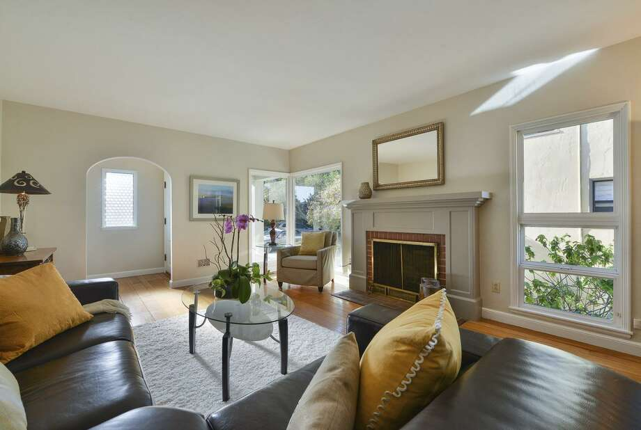Picture windows standing on opposite sides of the fireplace welcome natural light into the living room.