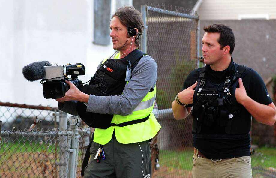 Cameraman Jack Cahill, with new reality TV show Live PD, films at a scene with the Bridgeport Police Department during an evening shift in Bridgeport, Conn. on Thursday Nov. 3, 2016. At right is Assistant Cameraman Nick Atwood. The shows offers viewers a live as-it-happens look into the routine of police departments in six cities all over the country. Photo: Christian Abraham / Hearst Connecticut Media / Connecticut Post