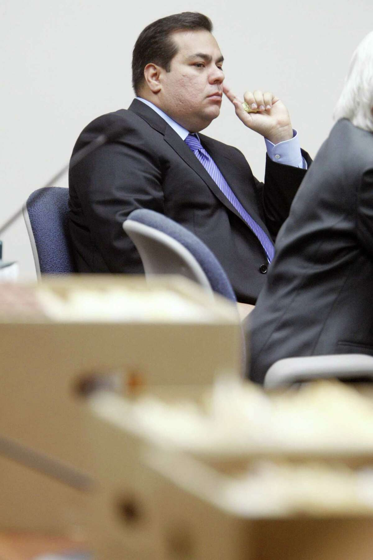 Defendant Mauricio Celis listens to testimony as boxes of the prosecution's documents line the tables Tuesday, Feb. 10, 2009, during the opening day of the first criminal trial against Celis at the Nueces County Courthouse in Corpus Christi. Celis is facing 23 counts of falsely holding himself out as a lawyer. (AP Photo/Corpus Christi Caller-Times,/Michael Zamora)