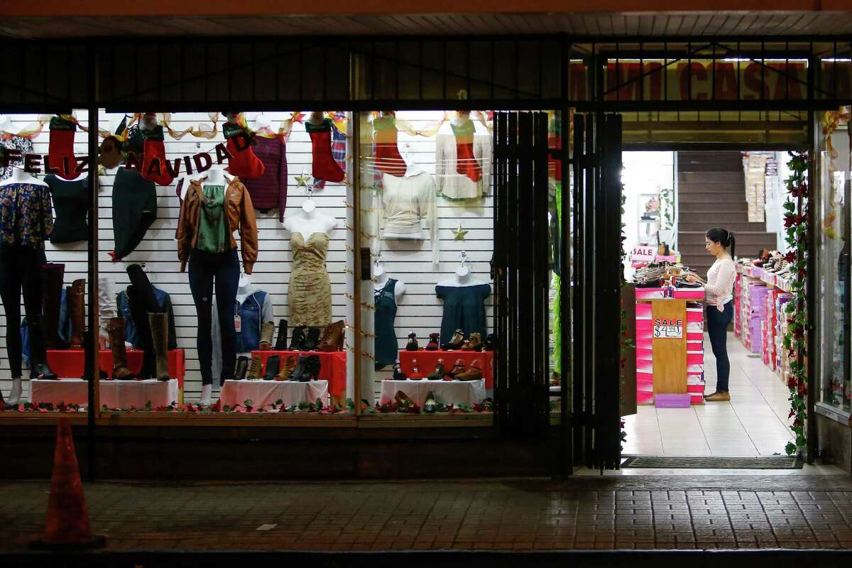 An employee stands inside a downtown Brownsville clothing store in 2016. Store owners in border towns such as Brownsville and McAllen are noticing a drop in sales as the peso declines in value against the U.S. dollar.