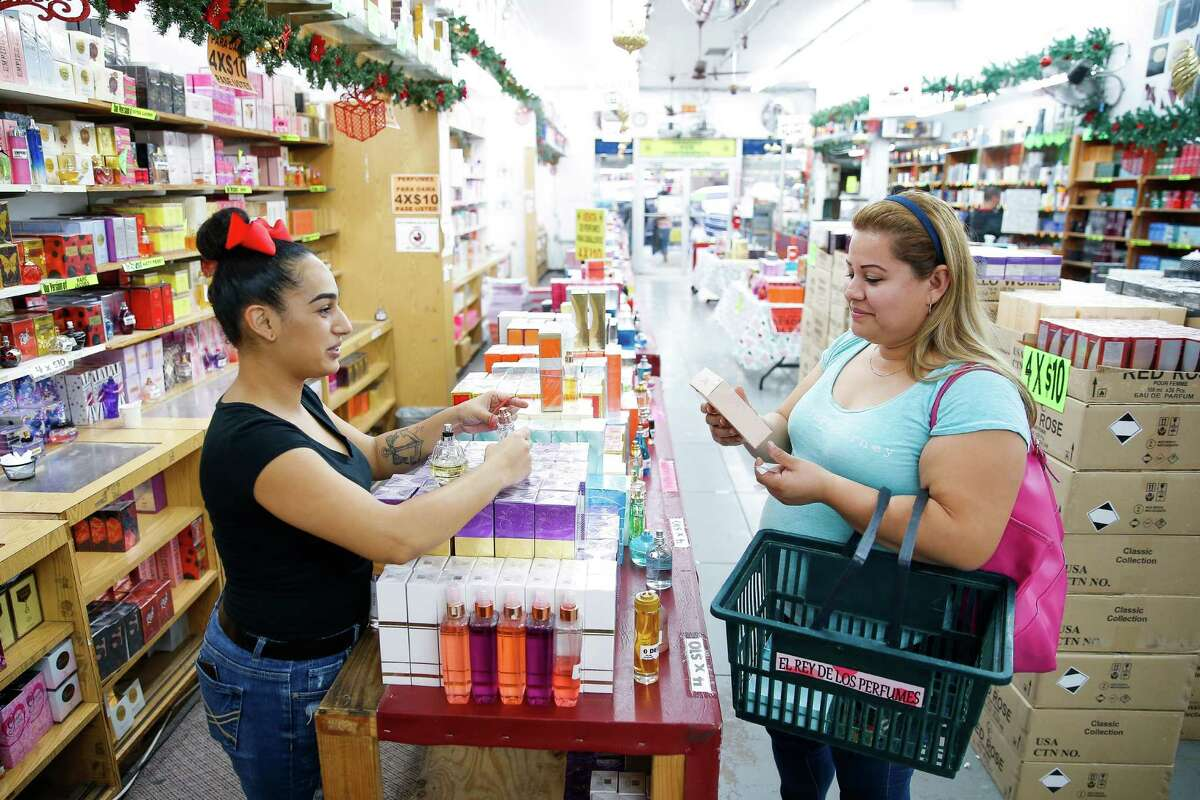 Perfume King sales associate Girelys Camacho, left, helps Jessica Hernandez pick out a perfume on her shopping trip to McAllen from Mexico in December 2016. Store owners in border towns such as McAllen are noticing a drop in sales as the peso declines in value against the US dollar.