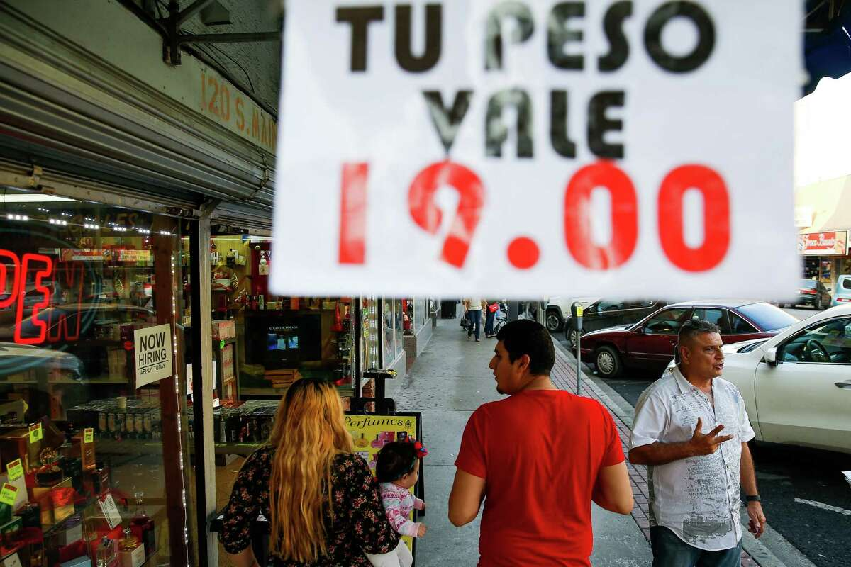 Perfume King owner Suresh Mansinghani, right, stands outside his store in McAllen, where he is advertising a better exchange rate for the peso earlier this month to entice Mexican shoppers.