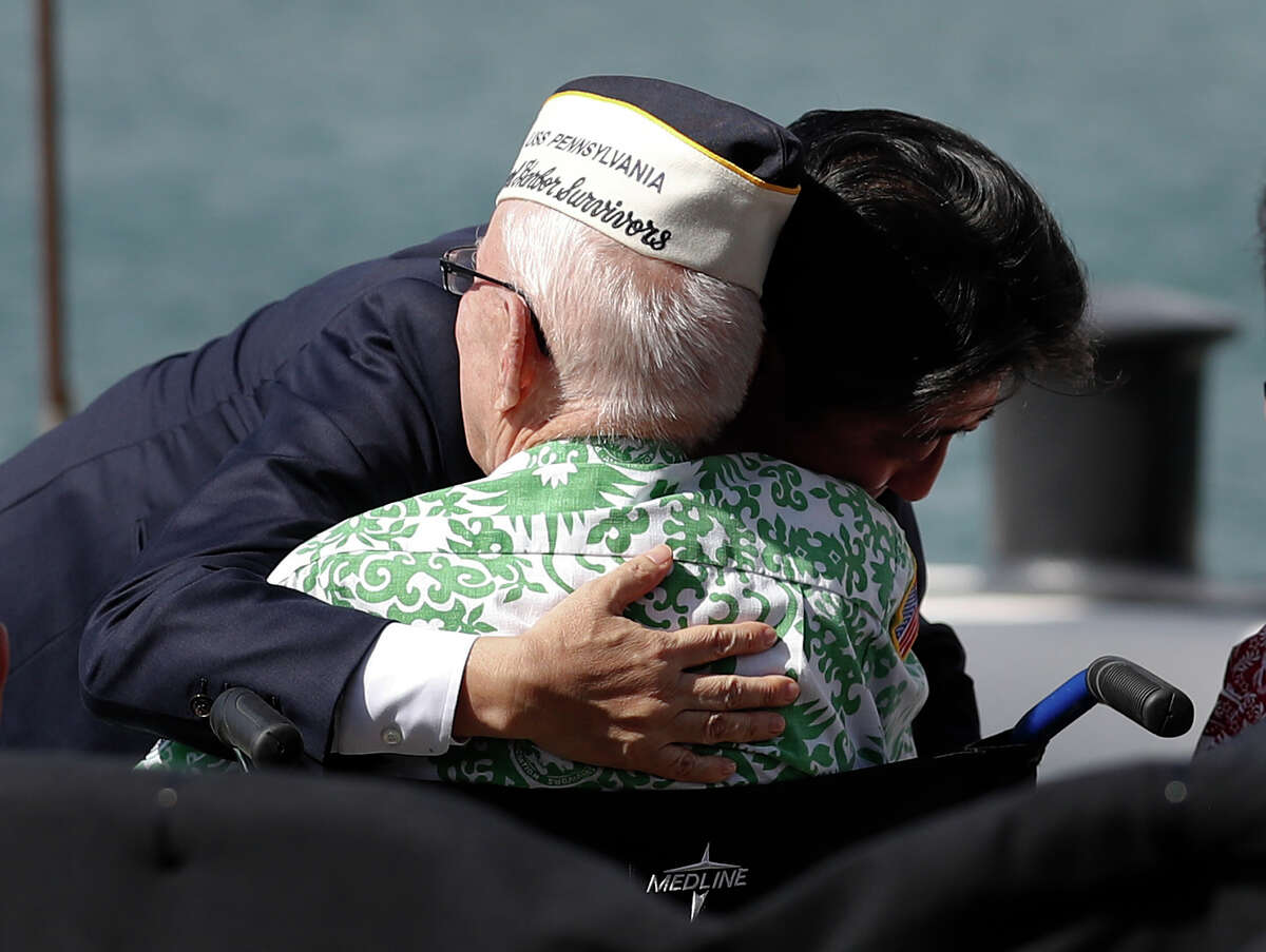 Japanese Prime Minister Shinzo Abe embraces a World War II Pearl Harbor survivor after he and U.S. President Barack Obama spoke on Kilo Pier, overlooking the USS Arizona Memorial, at Joint Base Pearl Harbor-Hickam, Hawaii, Tuesday, Dec. 27, 2016. Abe and Obama made a historic pilgrimage Tuesday to the site where the devastating surprise attack sent America marching into World War II.