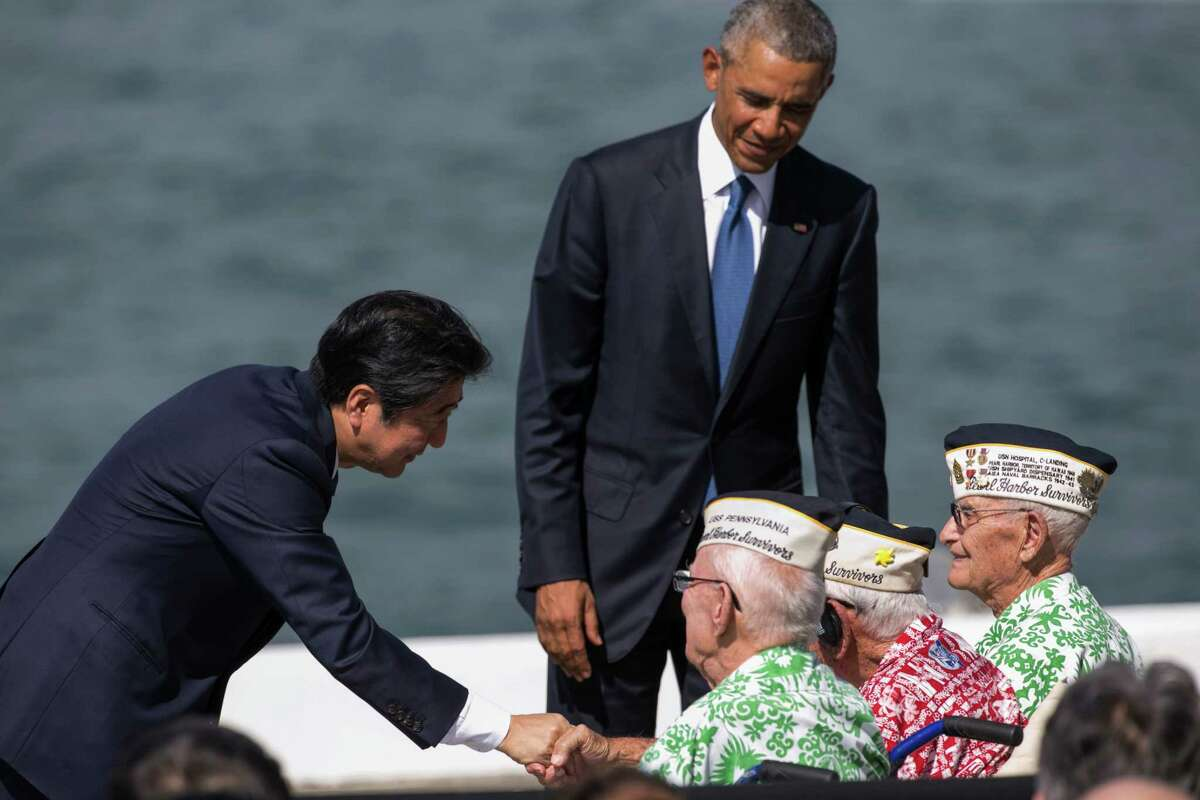 Japanese Prime Minister Shinzo Abe, left, and U.S. President Barack Obama speaks with Pearl Harbor veterans, all seated from left, Sterling Cale, Al Rodrigues and Everett Hyland at Joint Base Pearl Harbor Hickam, Tuesday, Dec. 27, 2016, in Honolulu. Abe and Obama made a historic pilgrimage Tuesday to the site where the devastating surprise attack sent America marching into World War II.