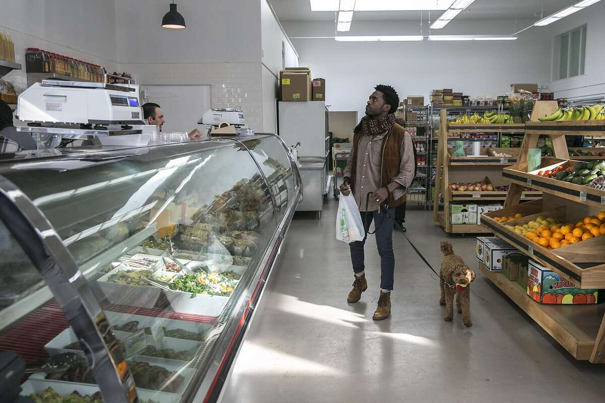 Lowell Caulder checks out the deli with his dog Moses at Luke's Local on Tuesday, Dec. 27, 2016 in San Francisco, Calif.