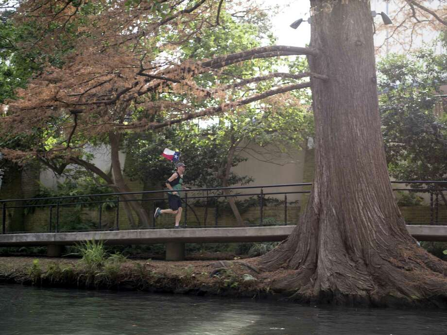 "Ultra runner and health activist Jim Plunkett-Cole runs down the riverwalk in downtown San Antonio during his run to raise awareness about childhood obesity on Tuesday, December 27, 2016. Cole decided to base the route he's running on the fictional character Forest Gump's route in the movie, ""Forest Gump."" Cole began the run in October and averages 20 miles a day. He has been stopping at various schools on his way to talk to children about his run and about staying in shape to fight childhood obesity. Photo: Matthew Busch, For The San Antonio Express-News / For The San Antonio Express-News / © Matthew Busch"