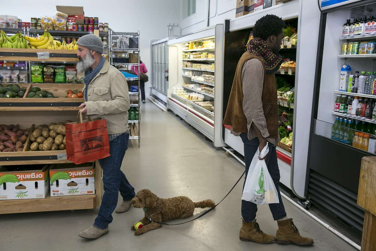 From right: Lowell Caulder with his dog Moses check out the bottled drinks as Bradley Burch makes his way to the produce section at Luke's Local on Tuesday, Dec. 27, 2016 in San Francisco, Calif. Caulder and Burch both live in the neighborhood.
