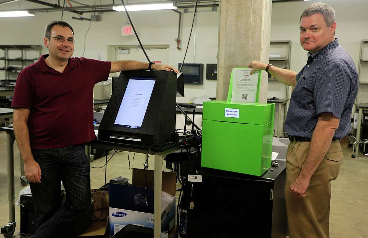 Rice University's Dan Wallach, left, and Phil Kortum show off a prototype of the STAR Vote machine, which records an electronic vote, then prints a copy of the paper ballot.