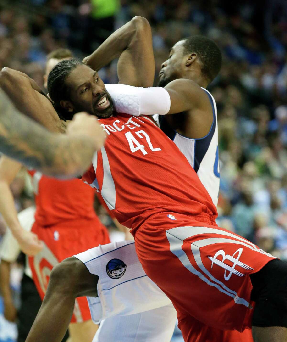 Houston Rockets center Nene Hilario (42) gets tangled up with Dallas Mavericks forward Harrison Barnes (40) while chasing the rebound during the first half of an NBA basketball game in Dallas, Tuesday, Dec. 27, 2016. (AP Photo/LM Otero)