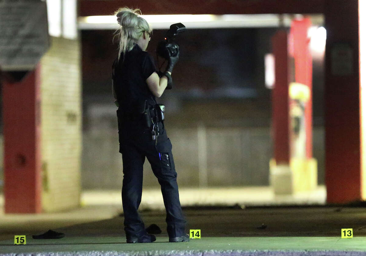 A crime scene investigator works Tuesday December 27, 2016 with her camera next to the Right Choice Food Mart on the 8,000 block of Midcrown where a shooting took place. At least one person was shot in the hand Tuesday night during a shootout at a Northeast Side gas station left littered with shell casings.