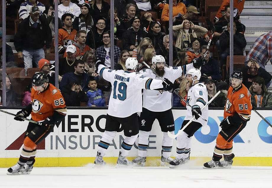 The Sharks' Brent Burns, center, celebrates his overtime goal in Anaheim with Joe Thornton (19) and Joe Pavelski. Burns leads NHL defensemen with 14 goals. Photo: Jae C. Hong, Associated Press