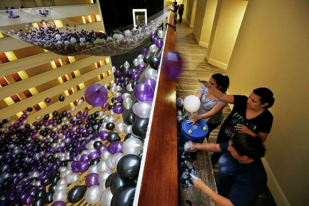 Oralia Valdez (bottom), Maria Garcia (middle) and Danyelle Valdez (top), with Fantastic Balloons, fill one of two giant nets with over 50,000 balloons for the Hyatt Regency Houston hotel's annual New Year's Eve party and balloon drop, Wednesday, Dec. 30, 2015, in Houston. ( Mark Mulligan / Houston Chronicle )