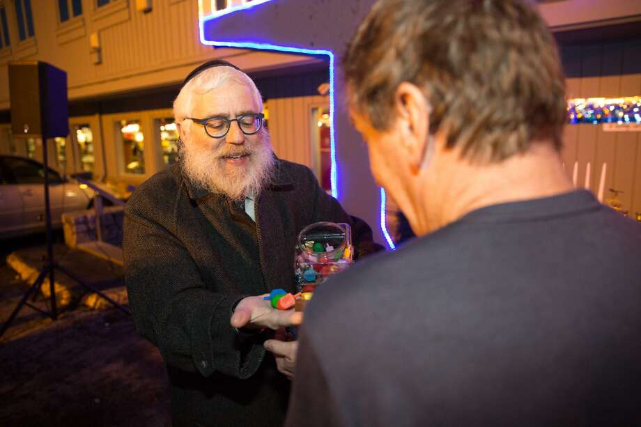 Rabbi Yehoshua Hecht hands out dreidels before the menorah lighting to celebrate the fourth night of Hanukkah at Stew Leonards in Norwalk, Conn. on December 27, 2016. Photo: Chris Palermo / For Hearst Connecticut Media / Norwalk Hour Freelance