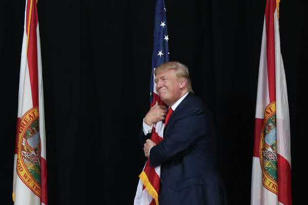 Republican presidential candidate Donald Trump hugs the American flag as he arrives for a campaign rally at the MidFlorida Credit Union Amphitheatre on October 24, 2016 in Tampa, Florida. There are 14 days until the the presidential election.