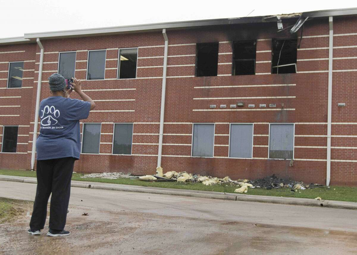 A woman takes pictures of a damaged section of Bear Branch Junior High School after a fire broke out around 12:20 a.m. Wednesday, Dec. 28, 2016, in Magnolia.