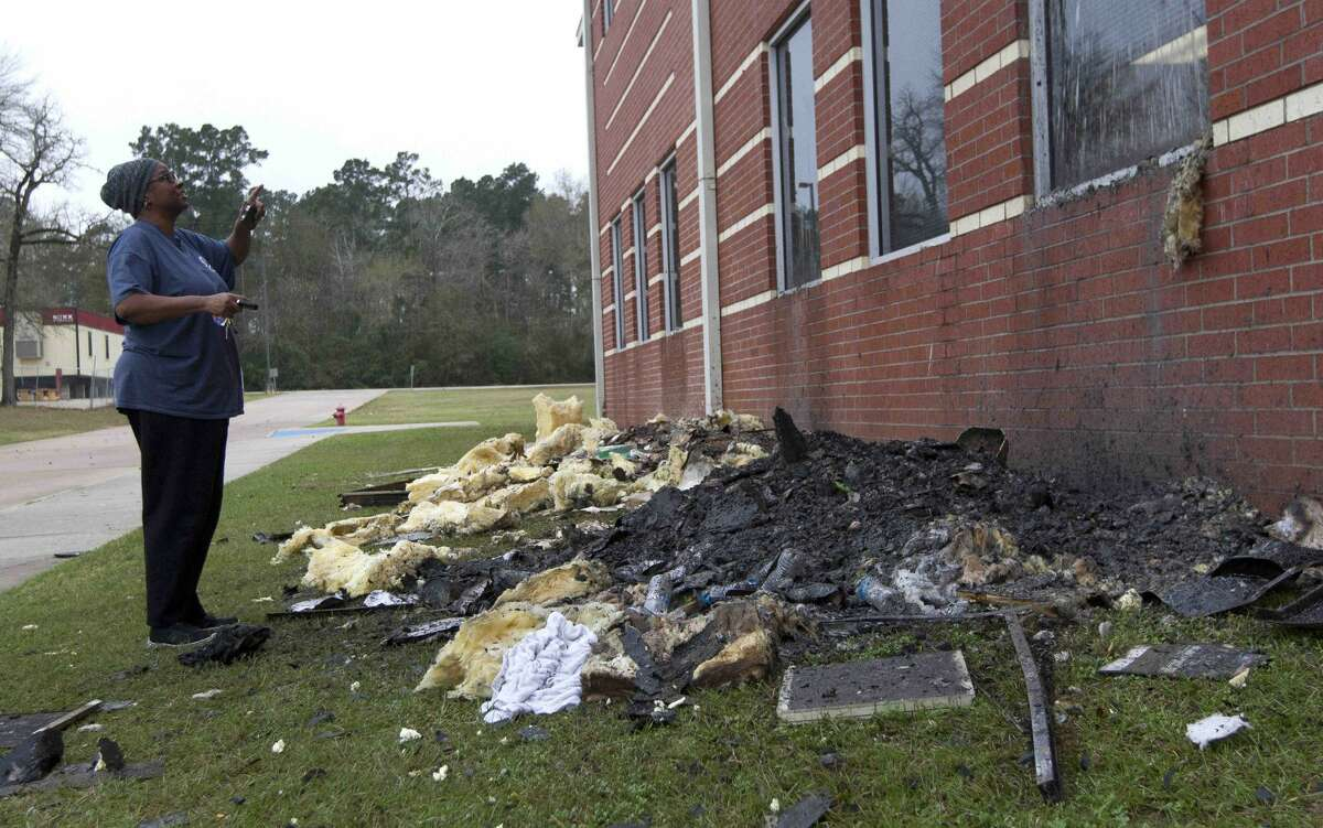 A woman surveys a damaged section of Bear Branch Junior High School after a fire broke out around 12:20 a.m. Wednesday, Dec. 28, 2016, in Magnolia.