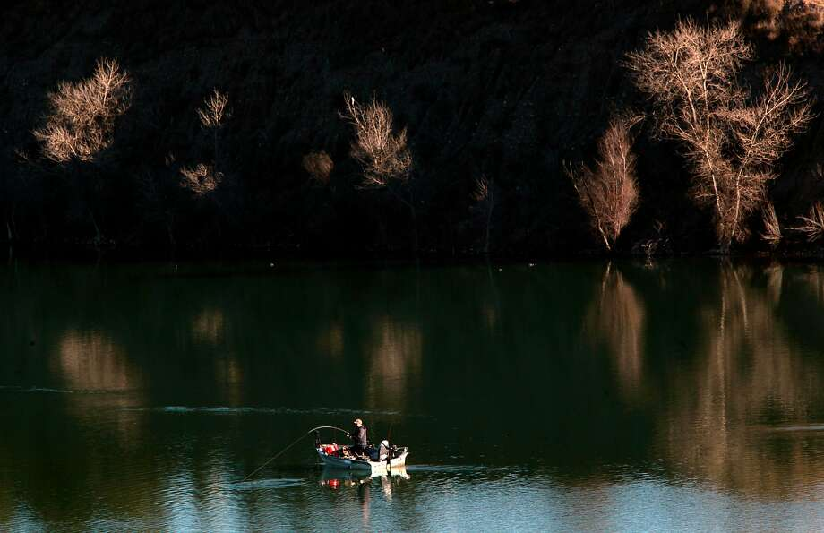 A fisherman hooks a fish on the still waters of Shadow Cliffs Regional Park in Pleasanton , California, on Wednesday December 28, 2016. A cold front is expected to hit the Bay Area just in time for New Years with temperatures in some areas dropping to the 20s to upper 30s, forecasters said. Photo: Michael Macor, The Chronicle